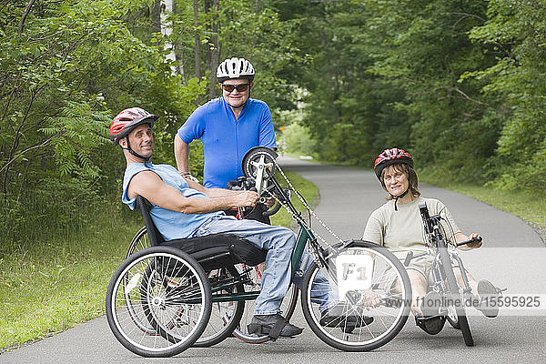 Portrait of a young man with a Spinal Cord Injury and his friends on adaptive bikes