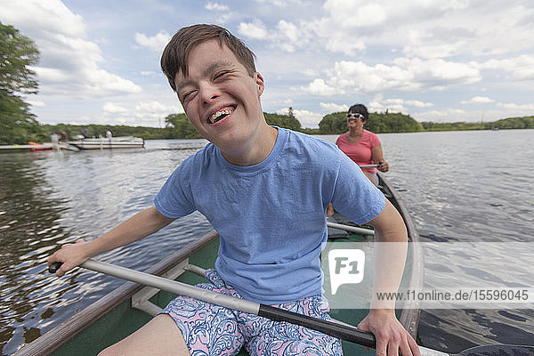 Happy young man with Down Syndrome rowing a canoe with his friend in a lake