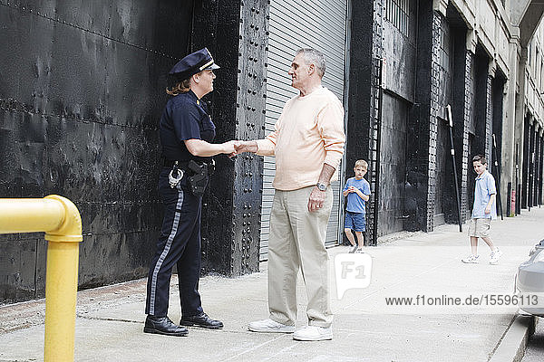 Woman police officer greeting a senior man.