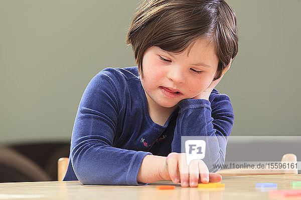 Little girl with Down Syndrome playing a learning game