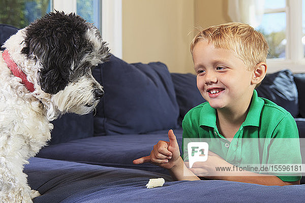 Boy with hearing impairments signing 'stay' in American sign language on their couch