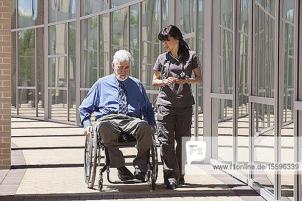 Man with muscular dystrophy and diabetes in his wheelchair walking with nurse using smart phone