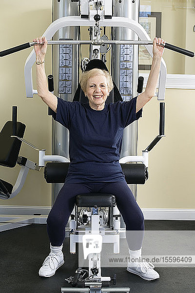 Senior woman working out on exercise equipment in a gym