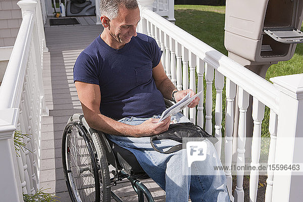 Man with spinal cord injury in a wheelchair getting his mails