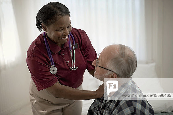 Happy female nurse comforting an elderly patient at his bedside