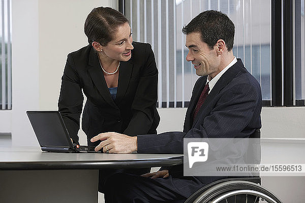 Businessman with spinal cord injury working on laptop with a businesswoman