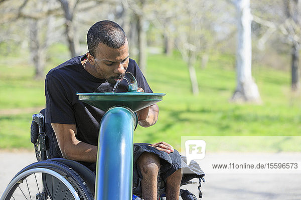 African American man with Cerebral Palsy using his cell phone at home