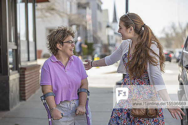 Woman with Cerebral Palsy walking with her sister in town