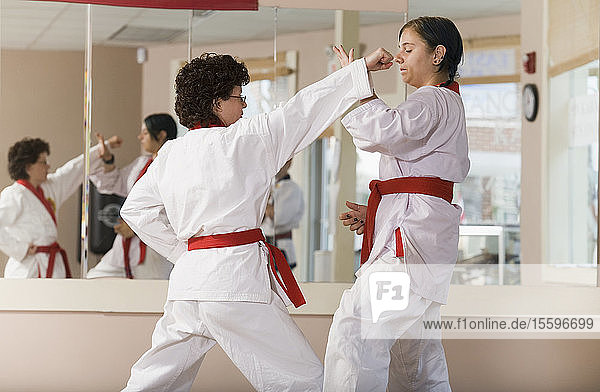 Young woman practicing karate with a mid adult woman