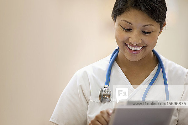 Portrait of young female nurse writing on a clipboard