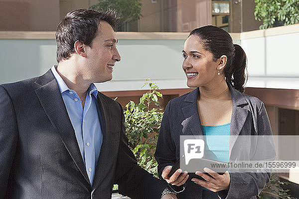 Business couple talking and holding tablet