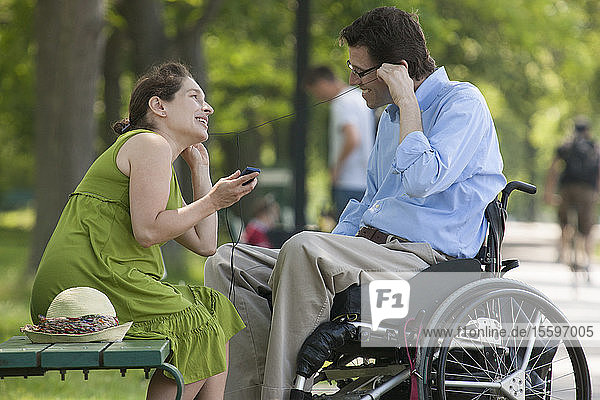 Pregnant wife with husband in wheelchair with spinal cord injury listening to an MP3 player