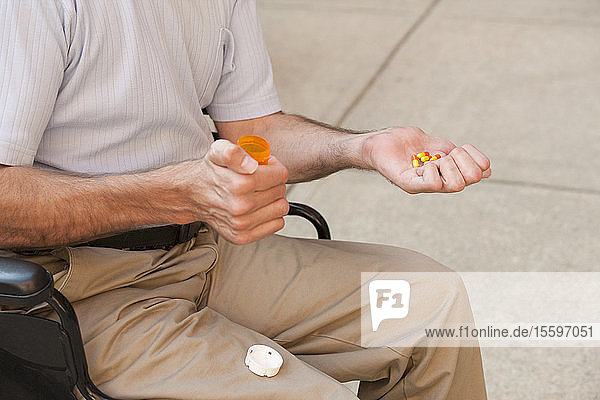 Man with Friedreich's Ataxia holding pills with degenerated hands