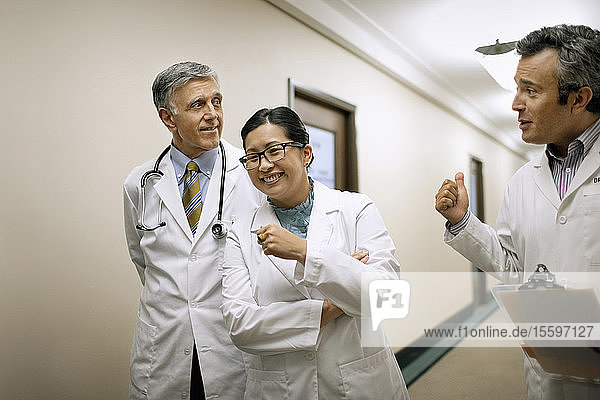 Medical colleagues laughing and talking in the corridor of a hospital