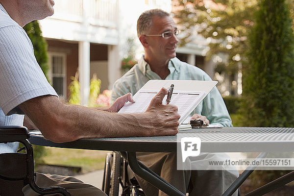Man with Friedreich's Ataxia holding a pen with degenerated hands sitting with a man with spinal cord injury