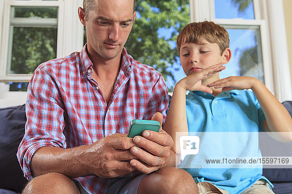 Father and son with hearing impairments signing 'email' on cellphone in American sign language on couch