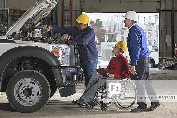 Power plant engineers one with spinal cord injury reviewing utility truck maintenance