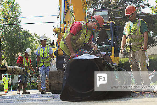 Construction workers cutting water main to length with gas powered saw