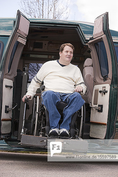 Man with spinal cord injury in a wheelchair coming out from a wheelchair accessible van