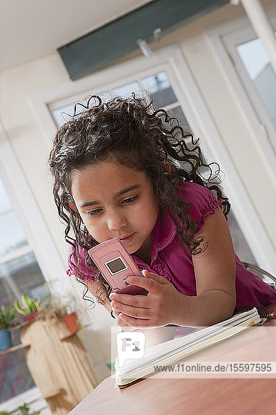 Hispanic girl using a mobile phone while doing school work