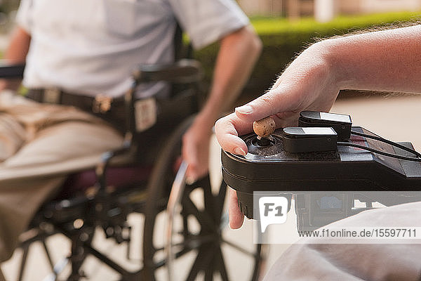 Man with Duchenne muscular dystrophy controlling a motorized wheelchair with degenerated hands