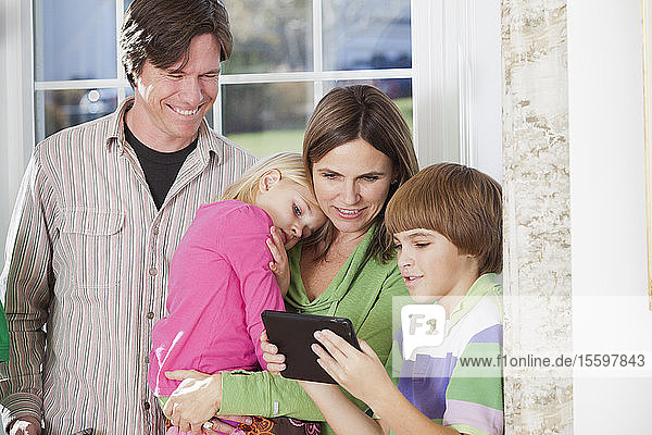Boy using a digital tablet with his parents beside him