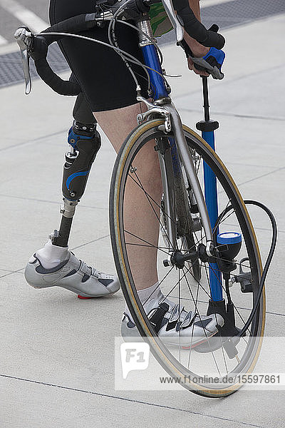 Woman with a prosthetic leg pumping air into a bicycle