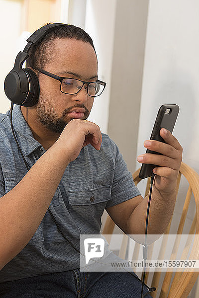 African American man with Down Syndrome listening to music on phone with headphones at home