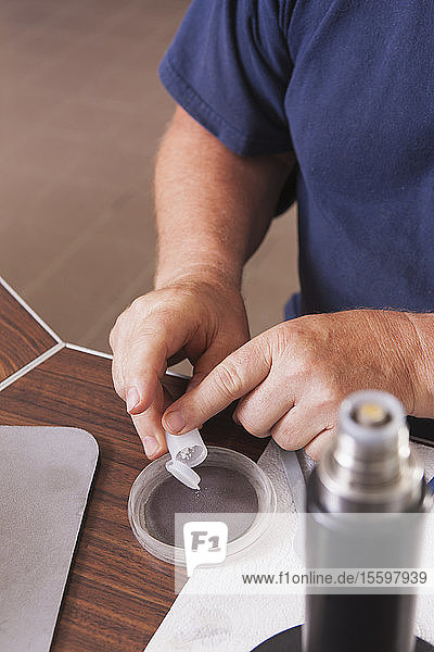 Engineer adding polishing powder to polishing pad with O2 electrochemical sensor in laboratory