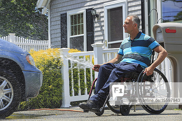 Man with a Spinal Cord Injury in wheelchair washing his accessible car