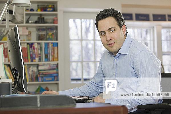 Hispanic businessman working on a desktop pc