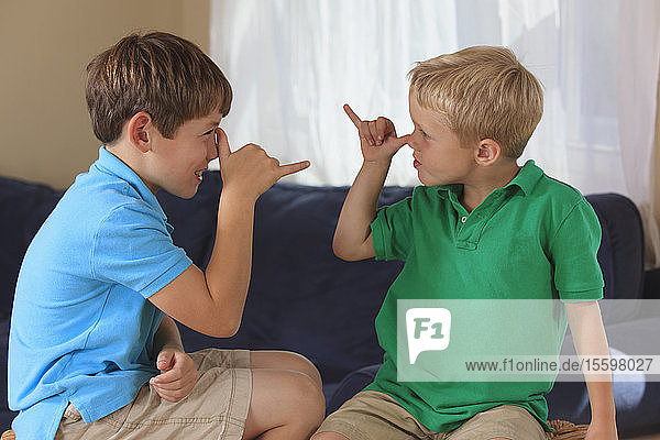 Boys with hearing impairments signing 'silly' in American sign language on their couch