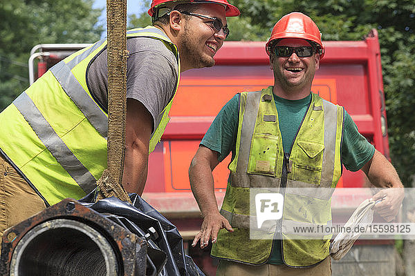 Construction workers guiding water main into place