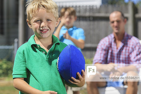 Happy boy with father and brother with hearing impairments playing football in backyard