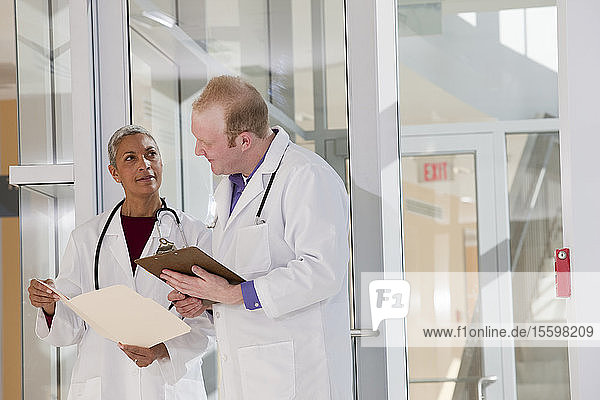 Two doctors discussing a medical report in hospital