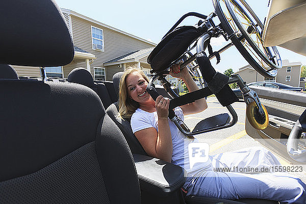 Woman with spinal cord injury lifting her wheelchair into her adaptive vehicle