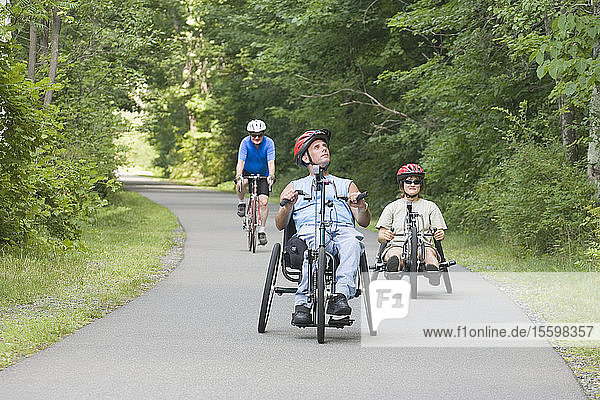Three friends riding adaptive bikes  one with a Spinal Cord Injury