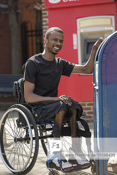 Man in a wheelchair who had Spinal Meningitis using the public mail box