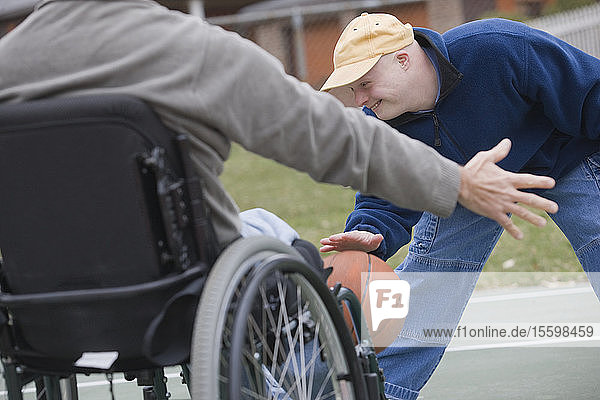 Disabled man playing basketball with his son Disabled man smiling with his son with Down Syndrome