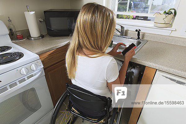 Woman with spinal cord injury in her accessible kitchen using a mobile phone