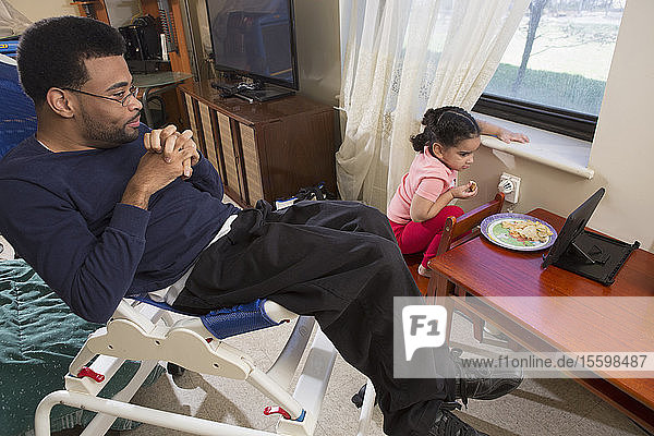 African American man with Cerebral Palsy with his daughter using a tablet at home