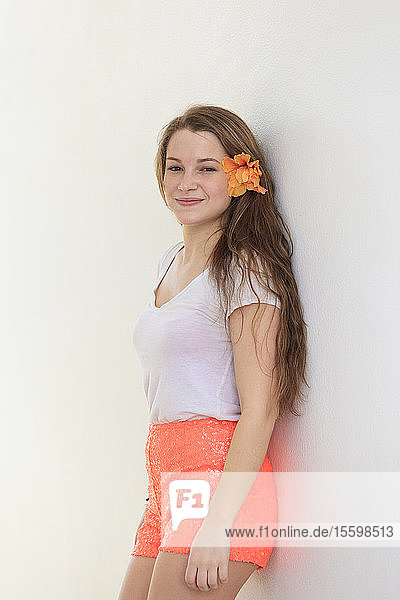 Smiling young woman leaning against a wall with flower in her hair