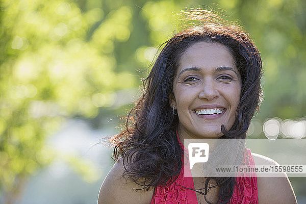Portrait of happy Hispanic woman smiling in a park