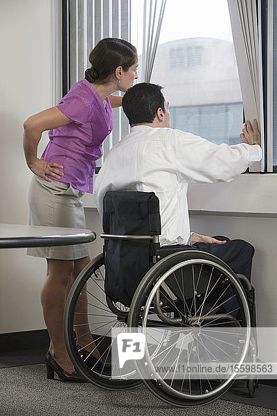 Businessman with spinal cord injury and a businesswoman looking through a window