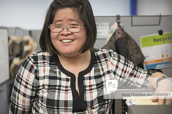 Asian woman with a Learning Disability using a file cabinet in office