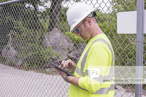 Engineer at an electric power plant checking his tablet