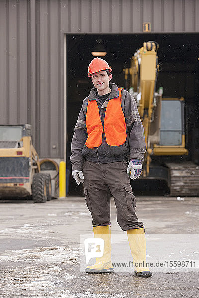 Transportation engineer standing at heavy construction equipment garage
