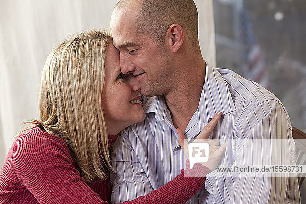 Woman signing the phrase 'I Love You' in American Sign Language while kissing a man