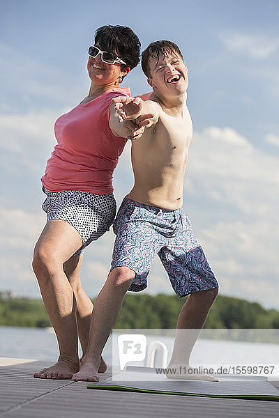 Young man with Down Syndrome exercising on a dock with his friend