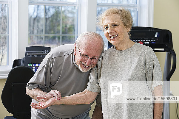 Senior couple smiling and checking pulse in the gym.